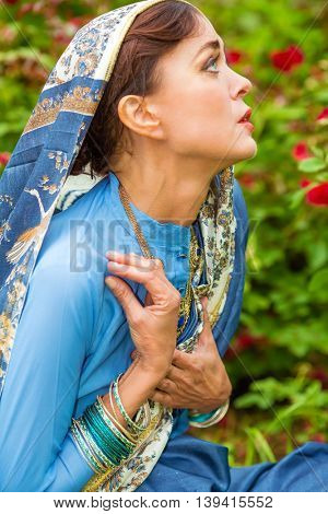 Middle age sad woman in blue sari and Indian adornment poses in garden