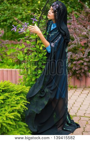 Middle age woman in black sari and Indian adornment walks in summer park
