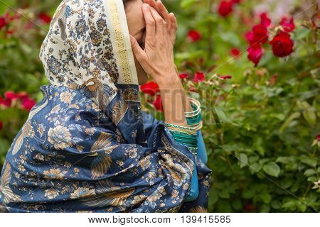 Woman in beautiful sari and necklace prays with closed face among rose bushes in park