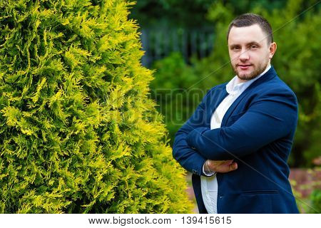 Unshaven handsome man in shirt and jacket poses in green summer garden