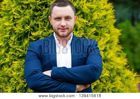 Unshaven handsome man in shirt and blue jacket poses in green summer garden