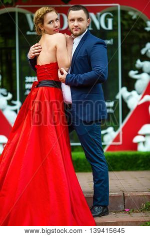 Man in suit and woman in red dress pose near wall with heart and text Wedding