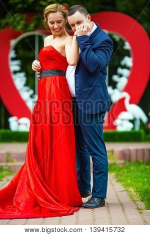 Man in suit kisses hand of woman in red dress near wall with big heart