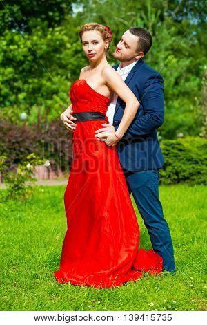 Man in suit and young woman in red dress pose on grass in summer garden