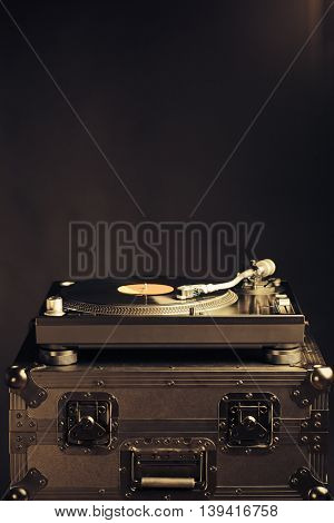 professional dj turntable on flight case, dark background