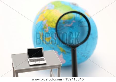 Notebook PC, magnifying glass and globe on white background. Global or international business concepts.
