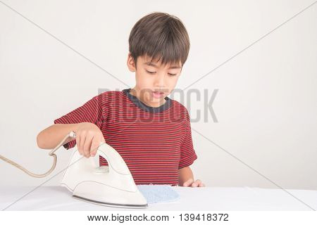 Little boy ironing his cloth helping of house work