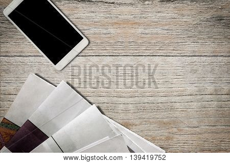Stack of newspaper and smartphone on wooden background.
