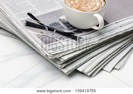 Stack of newspapercup of coffee and eyeglass on the table.