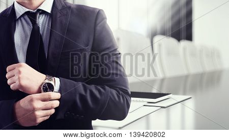 Businessman with clock and meeting desk on background