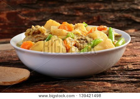 Chicken and vegetable stew on wooden background.