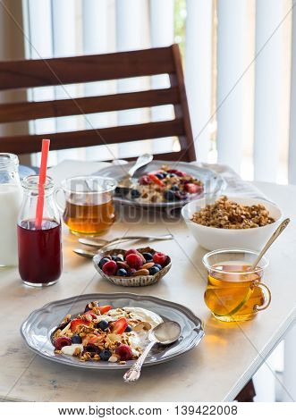 Healthy breakfast with greek yogurt fresh berries and granola. Served for two window on the background