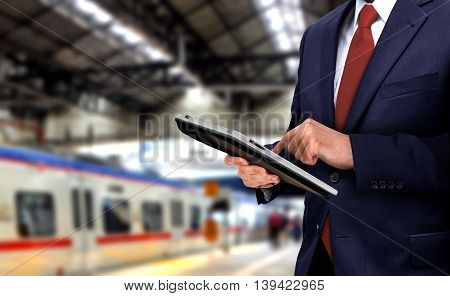 Businessman with touchpad at train station with blur background