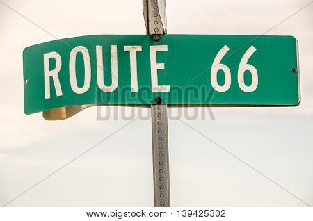 Street sign for Route 66 in Illinois with white letters on a green background against a partly cloudy sky