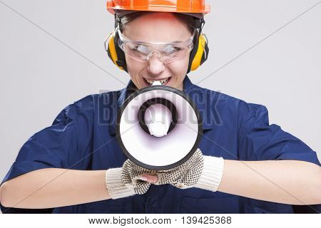 Expressive Caucasian Female Worker Posing with Megaphone and Wearing Hardhat for Protection. Horizontal Image Composition