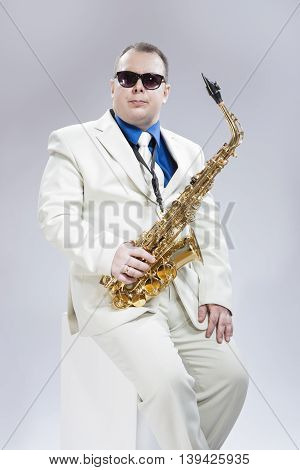 Music Concept and Ideas. Handsome Caucasian Musician With Alto Saxophone Posing In White Suit and Black Sunglasses Against White Background. Vertical Image Orientation