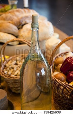the bottle of oil on the table, a basket of vegetables, flavor