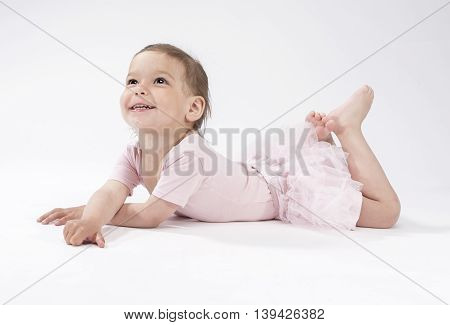 Lovely and Cute Caucasian Female Child Laying on Floor Against White Background. Smiling Happily. Horizontal Image