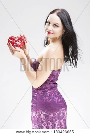Portrait of Sensual Brunette Woman Holding Symbolic Red Weaved Heart In Front. Over White Background. Vertical Image