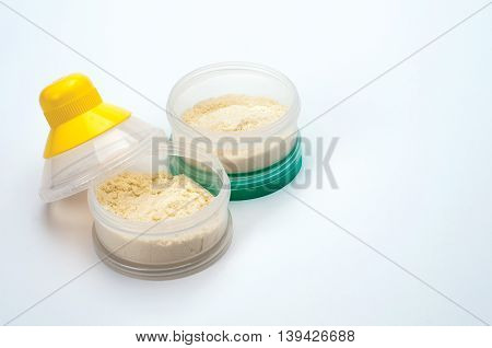 Container of powdered milk for infants on white background.