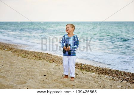 The little boy in the vest with the binoculars , walks on the beach