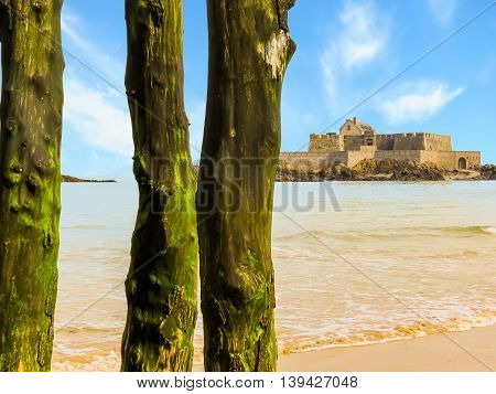 Old wooden breakwaters in low tide and Fort National. Seashore Saint-Malo, Brittany, France