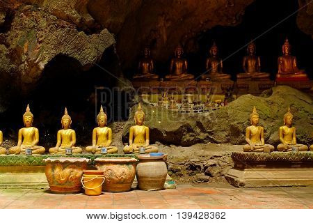 ROWS OF BUDDHA  IMAGES IN A CAVE Rows of Buddha images are placed peacefully in a cave.