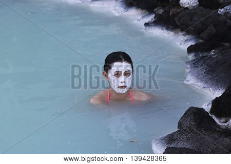 ICELAND - JULY 5, 2016: Geothermal spa visitors with silica mud masks relax and refresh at the famous Blue Lagoon in Iceland