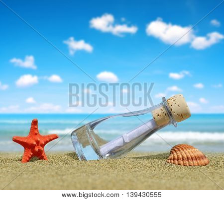 Bottle with a message, starfish and shell on sandy beach