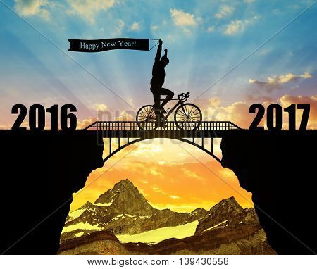 Cyclist riding across the bridge at sunset. Forward to the New Year 2017