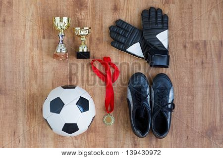 sport, achievement, championship and success concept - close up of soccer ball, football boots and goalkeeper gloves with golden medal and cups on wooden background