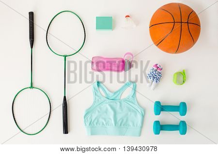 sport, fitness, healthy lifestyle and objects concept - close up of badminton rackets with basketball ball, speaker and sports stuff over white background