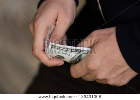 drug trafficking, crime, addiction, people and sale concept - close up of addict or dealer hands with dollar money and dose