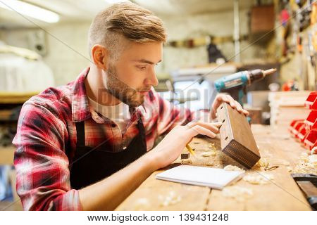 profession, carpentry, woodwork and people concept - carpenter working with wood plank at workshop