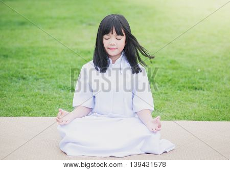 Beautiful Asian girl wearing white dress meditating in lotus position