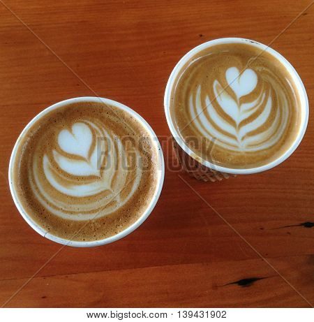 Two flat white coffees in disposable paper cups with latte art. Photographed at a farmers market in Kerikeri Northland New Zealand NZ.