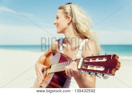 Beautiful young woman playing guitar on beach