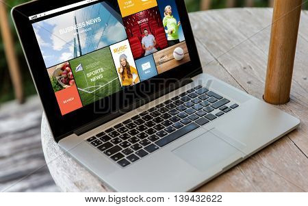 technology, internet, media, business and modern life concept- close up of open laptop computer with news web page on screen on table at hotel terrace