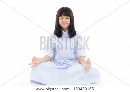 Beautiful Asian girl wearing white dress meditating on white background isolated