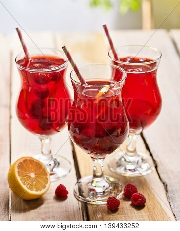 On wooden boards are three ice cold beverage glasses with red raspberry lemon cocktail . Alcohol country cocktail beverage number two hundred fourty with lemon. Group of raspberry cocktail on outdoor.