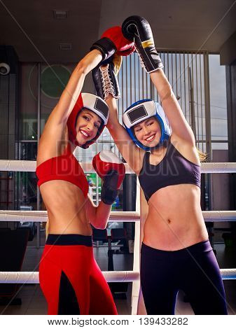 Two women boxer wearing gloves posing in boxer ring. Boxer women celebrating victory.