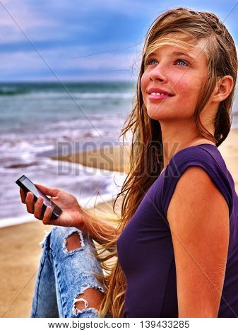 Girl with mobile phone sitting on sand near sea. First love of girl with phone sitting on sea beach