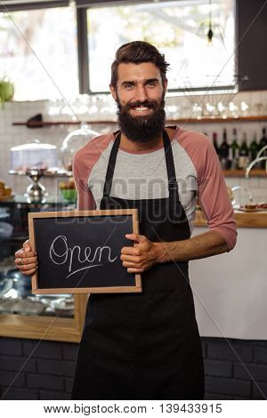 Waiter holding blackboard with open in the cafe