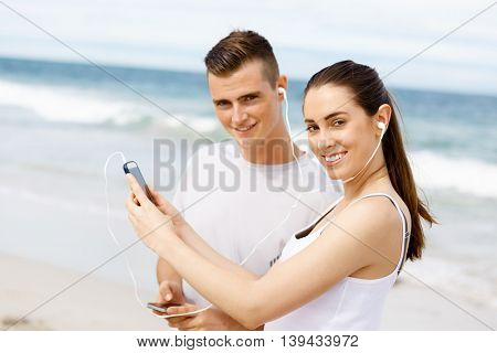 Couple of runners with mobile smart phones outdoors