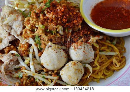 cayenne pepper and crushed bean on yellow noodle with pork ball