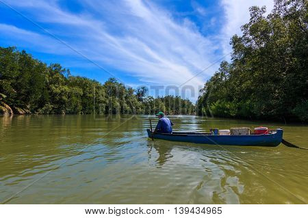 Tuaran, Sabah, Malaysia - May 28, 2016 : Fisherman riding on old boat at Mangrove Forrest river Image has grain or blurry and soft focus when view at full resolution. (Shallow DOF, slight motion blur)
