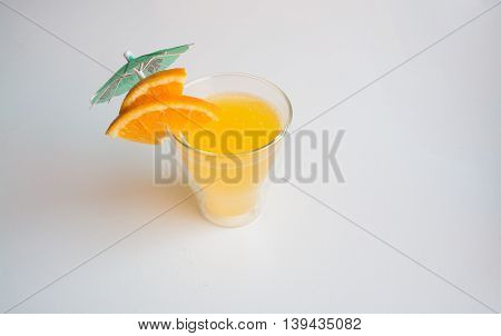 Orange soft drink with umbrella and orange wedges