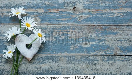 Daisy flowers with a heart shape on old wooden background