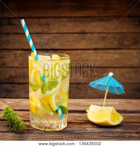 Drink with lemon, mint, ice, water on wooden background. Toned image.