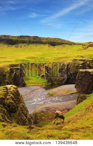 Neverland Iceland. Picturesque rocks with yellowed grass around the canyon Fjadrargljufur